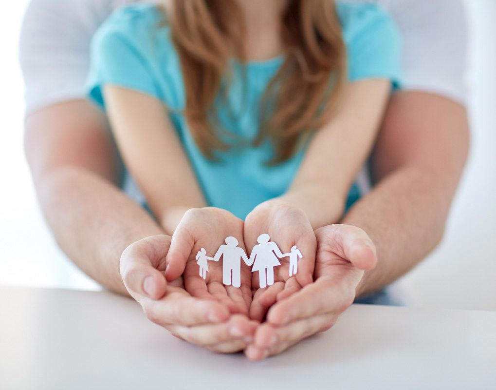 a child holds a paper cutout of a family while an adult cups her hands in his