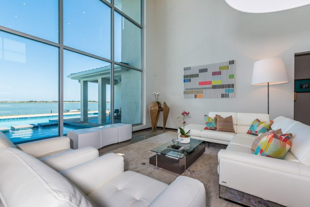 waterfront modern white luxury living space with floor to ceiling windows