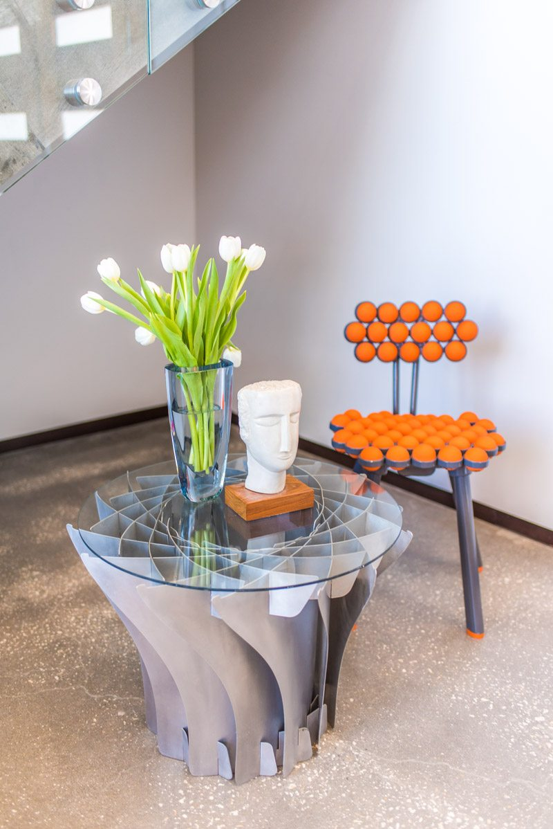 modern eclectic side table with bust and orange chair