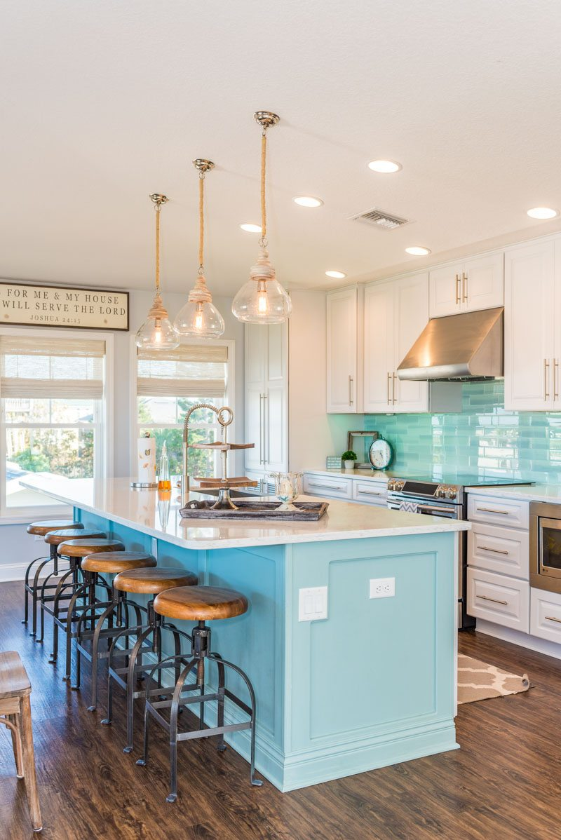 light blue kitchen bar with stools and teal backsplash