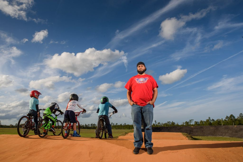 first coast bmx owner anthony sargent poses on the track with bmx riders