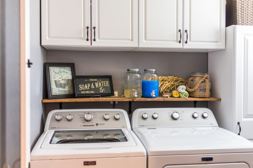 laundry room setup with open shelving and mason jar containers in las palmas condo st augustine