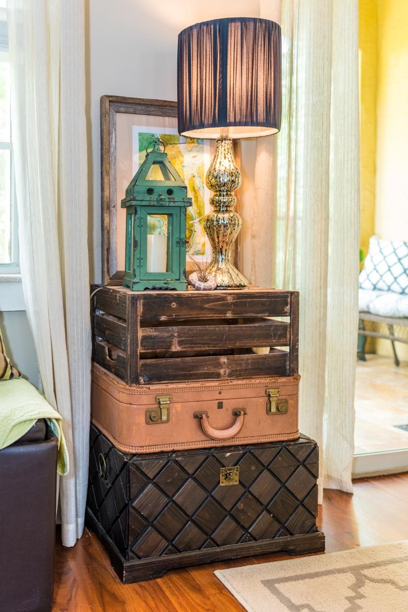 stacked boxes and trunks function as a table for a lamp and decor in las palmas condo st augustine