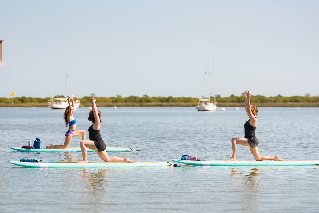 st augustine social team poses on the water with sup yoga center