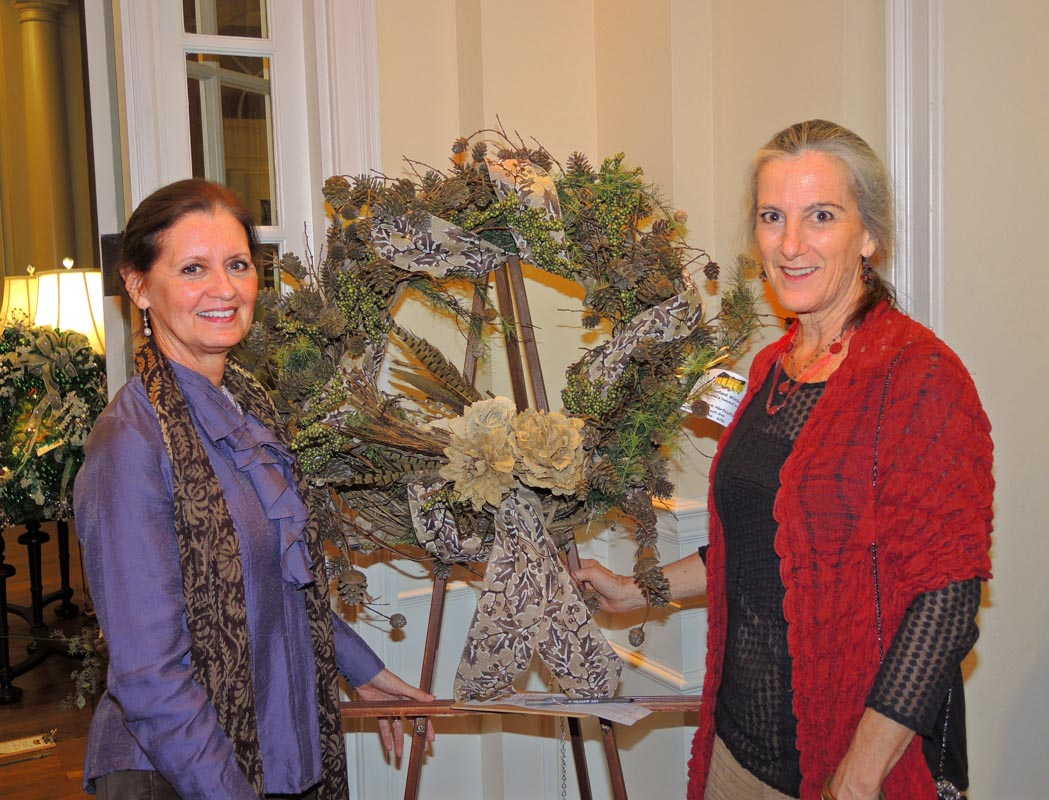 bryanne and jean stand by a decorated wreath at the council on aging christmas celebration
