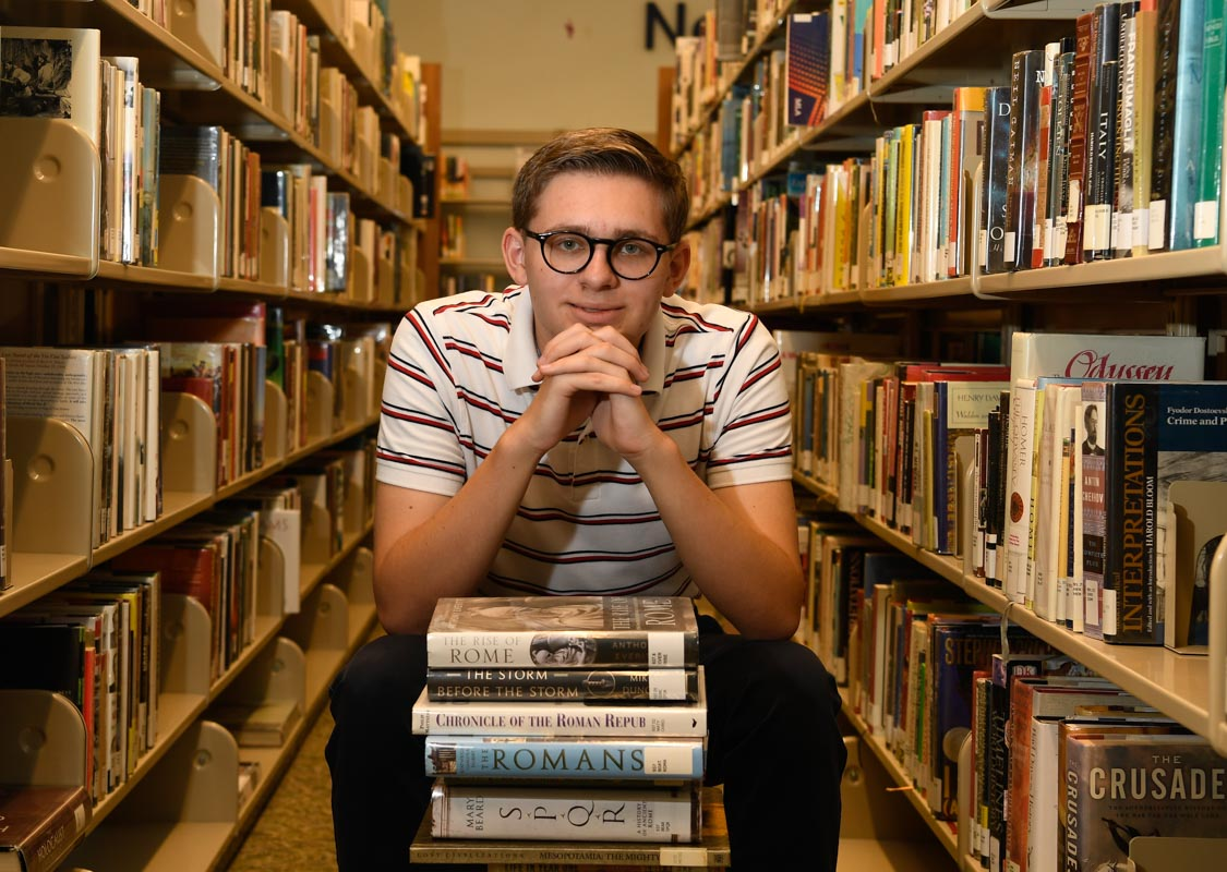 James Maynard an intern at the st johns county public library sits with a stack of books