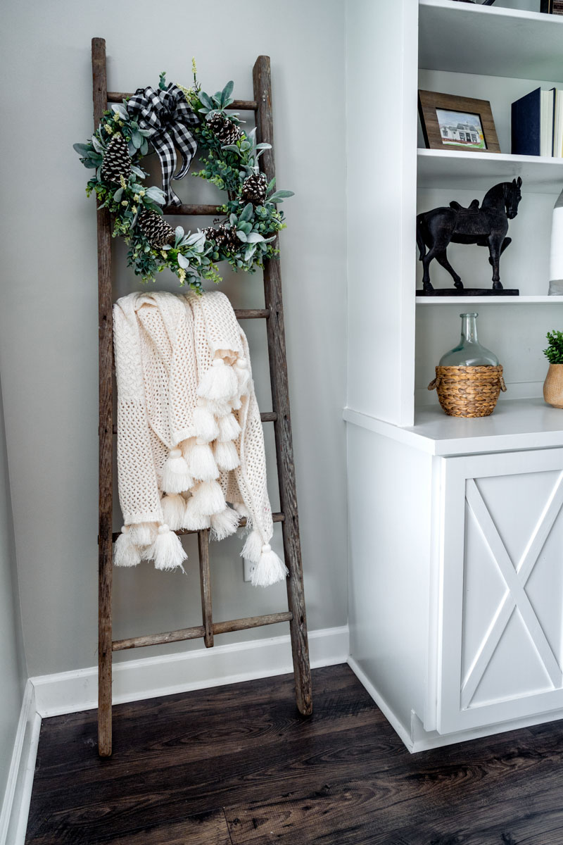 blanket and wreath on antique ladder in matt and tracy's st augustine farmhouse