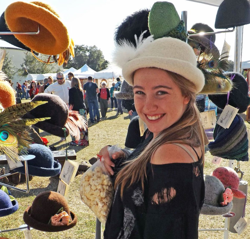 a guest at the st augustine festival of art tries on handmade hats