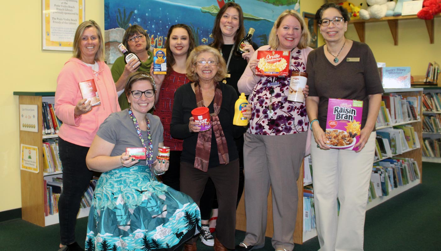 librarians hold donations for the st johns county library food for fines program
