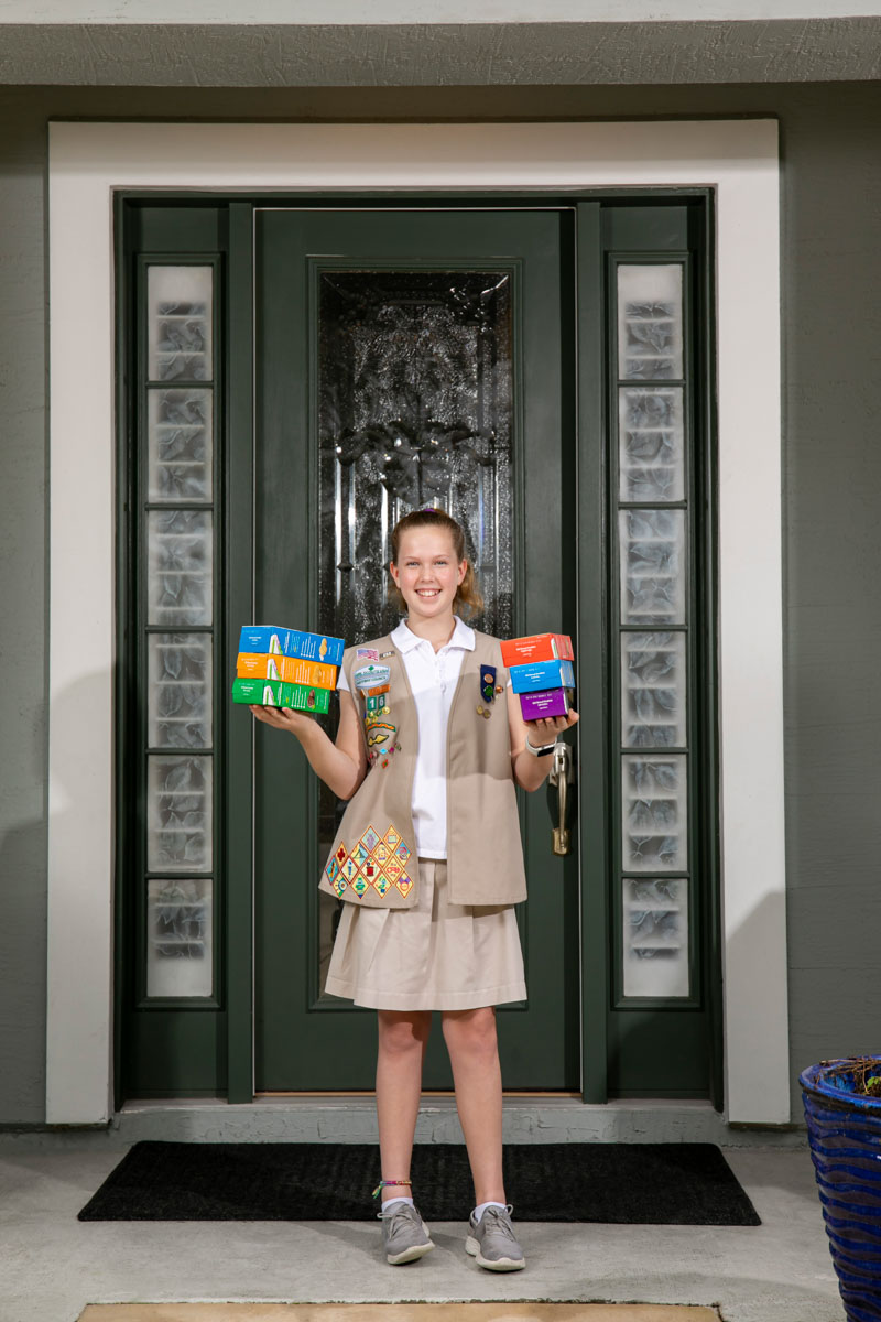 girl scout jane hershiser holds cookie boxes