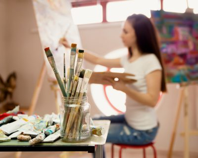 a young student paints in an art room