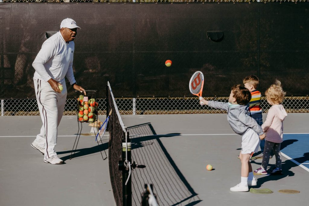 st augustine tennis instructor harold hardy plays tennis with some young students