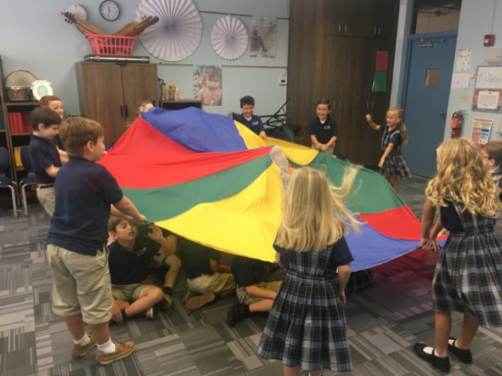 students at cathedral parish school in st augustine play with a large rainbow cloth