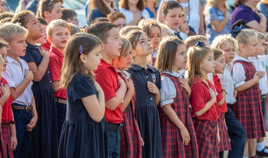 students at st johns academy salute the flag