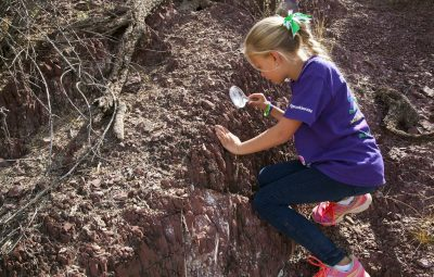 a young girl scout examines dirt with a magnifying glass