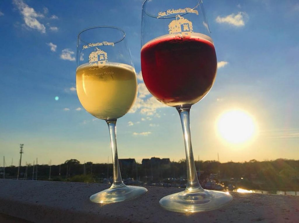 two glasses of red and white wine in front of the sun at san sebastian winery's cellar upstairs in st augustine