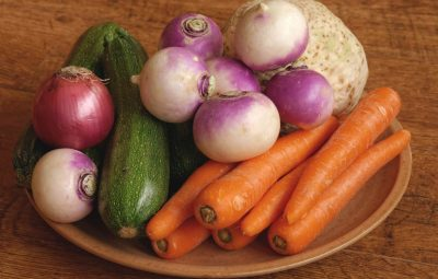 cucumbers carrots onions on a brown plate on a wood table