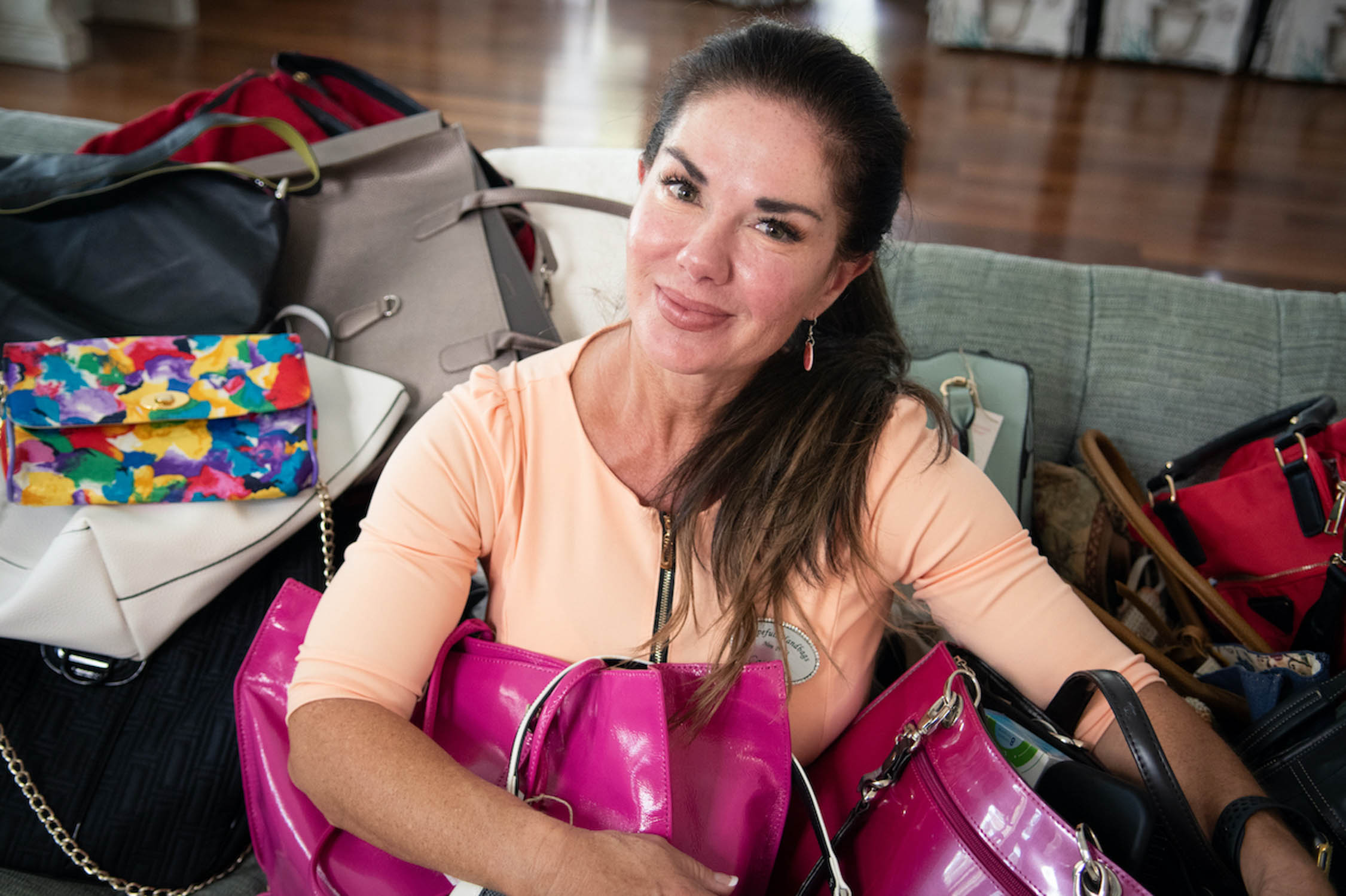 cathlene miner of hopefull handbags sits with some handbag donations