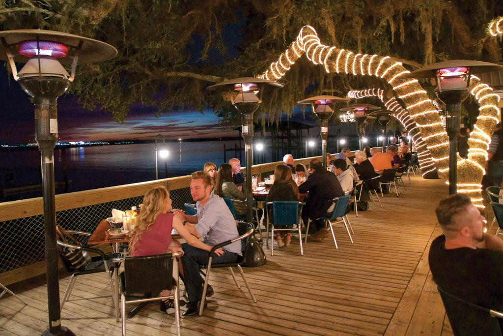 diners on the deck of caps on the water at night under lights