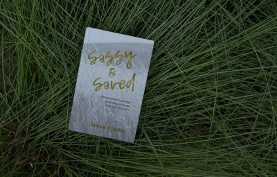 sassy and saved book sits in tall green grass