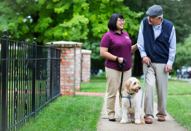 a senior carer walks with a senior and his dog