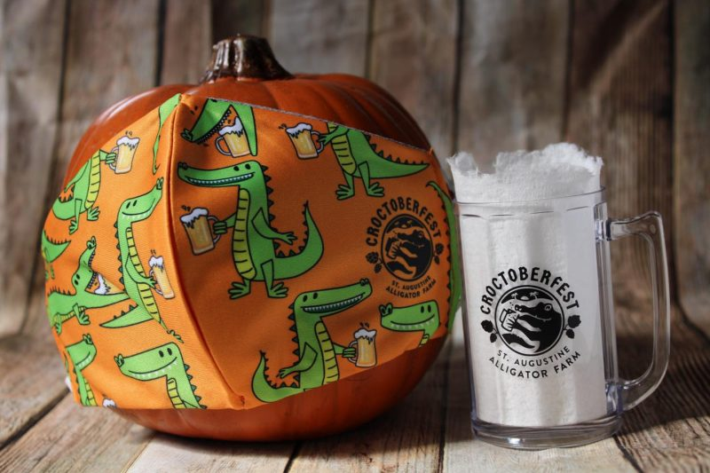 St. Augustine Alligator Farm celebrates Croctoberfest Brew at the Zoo 2020 with beer mug and pumpkin with themed alligator mask.