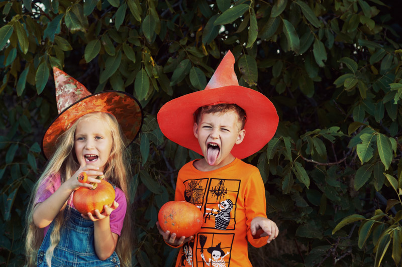 Kids dressed up for Halloween holding pumpkins and having fun outside.
