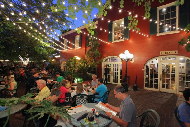 Guests at Harry's Seafood Bar & Grill in St. Augustine enjoy dinner on the outdoor patio under lights.