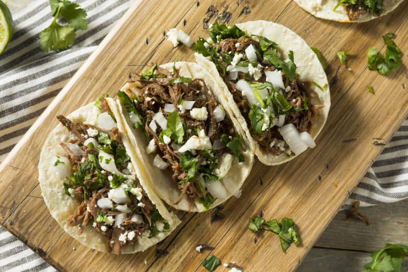 Three Beef Tacos with cilantro, cheese and onion.